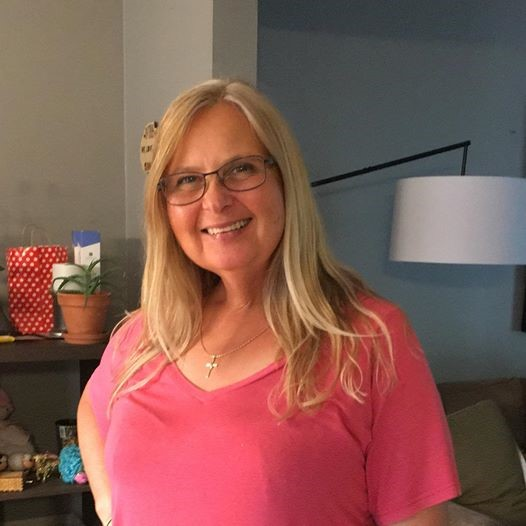 A woman stands in a pink t-shirt smiling. She has blonde hair and glasses.