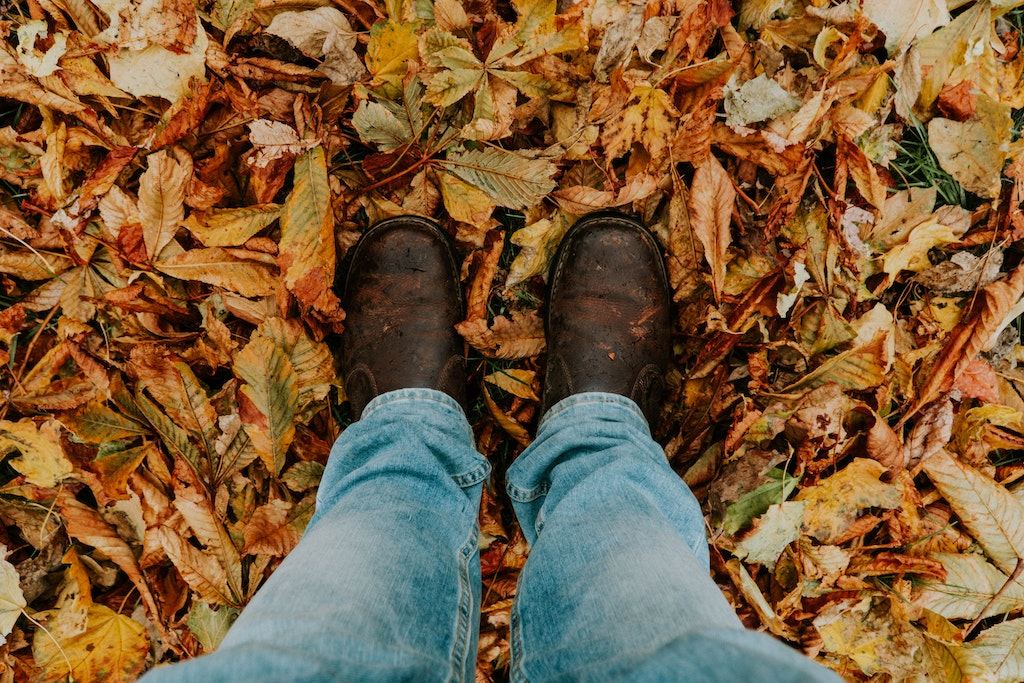 A man stands on red, orange and yellow leaves. He is wearing brown boots and blue jeans.