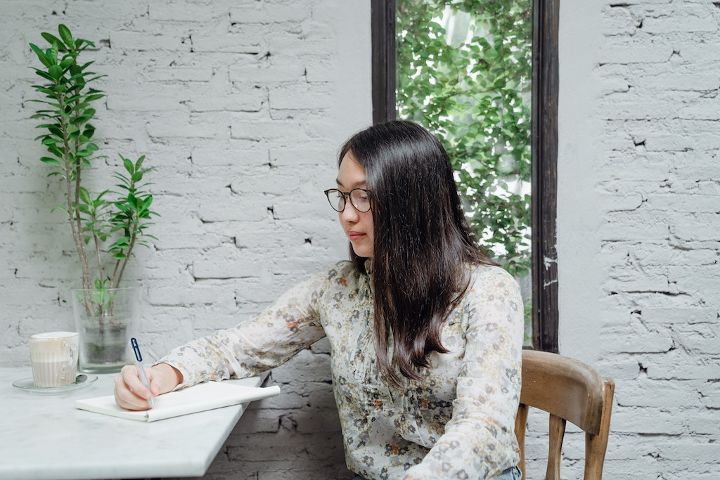 Girl wearing floral shirt and glasses writes with a pen at her desk against a white brick wall