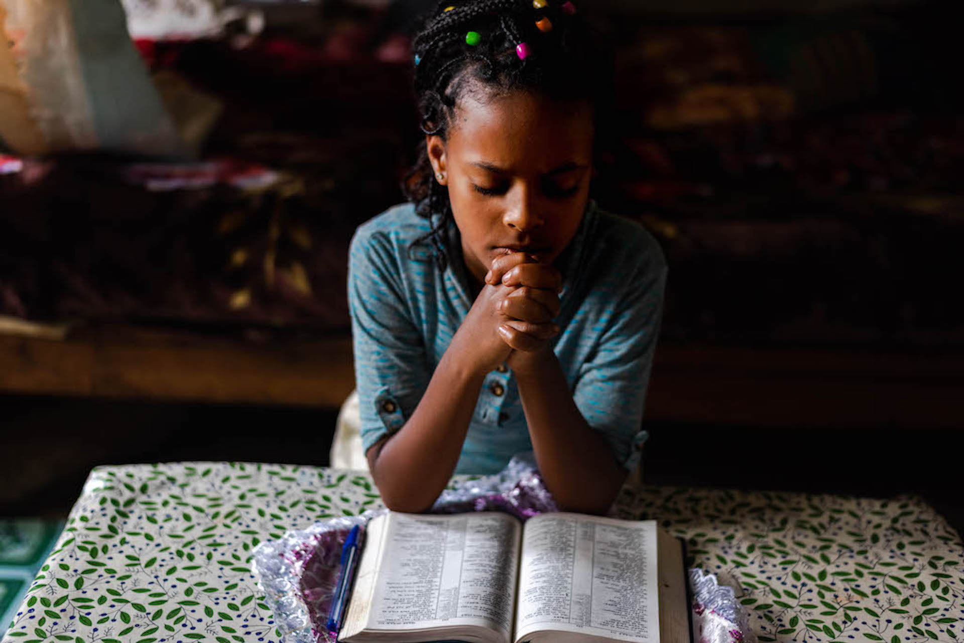 An Ethiopian girl praying with a Bible open on the table in front of her.