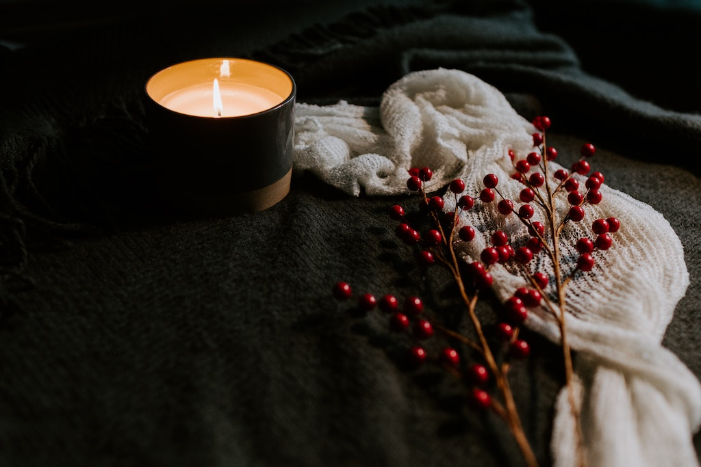 A candle sits beside a white scarf and a cranberry plant