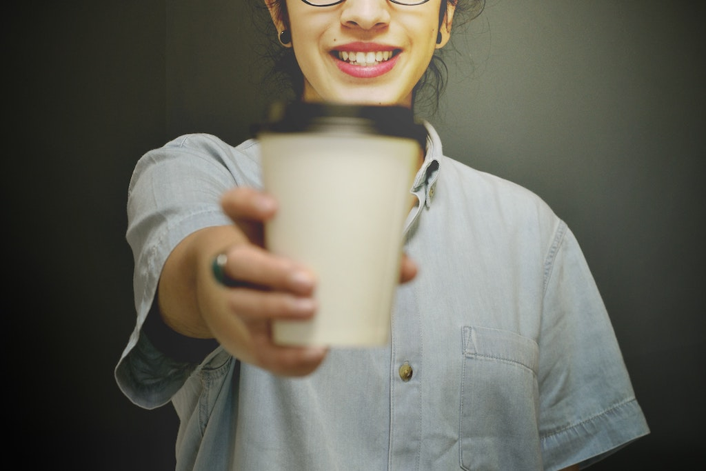 A girl wearing a denim shirt gives a coffee to the camera
