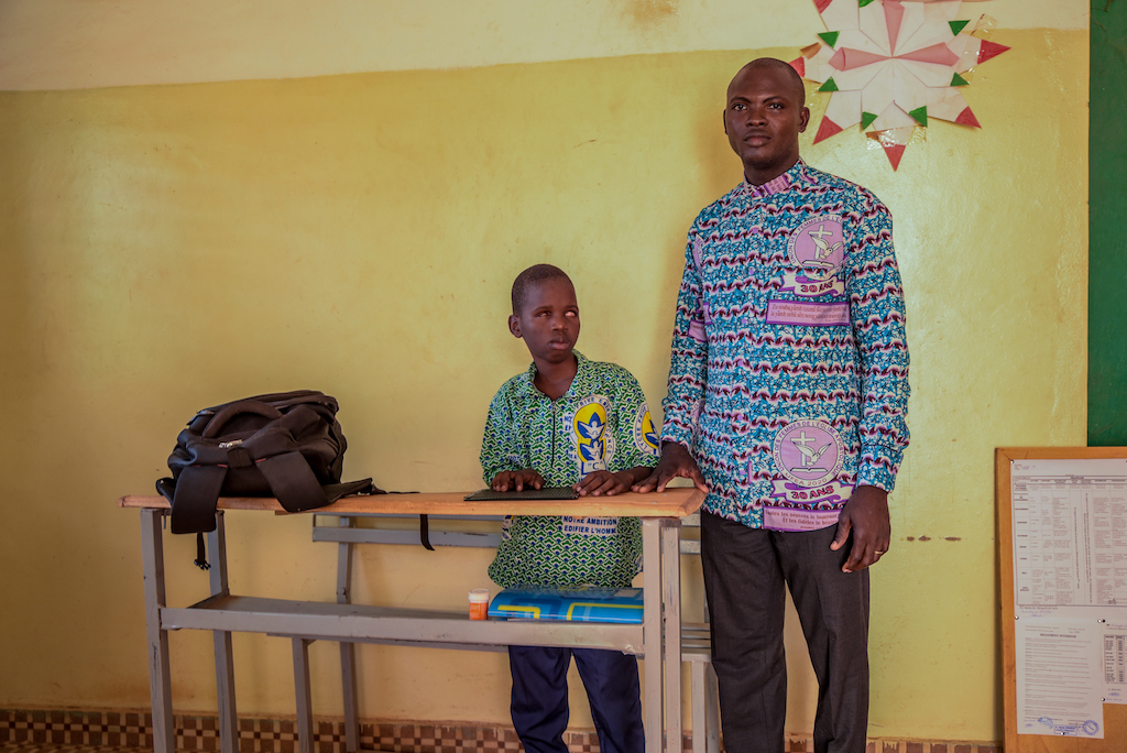 Kader is wearing a blue, white, and green patterned shirt. He is standing in his classroom with his teacher, Nana, who is wearing brown pants with a pink and blue patterned shirt. They are standing at a desk in front of a yellow wall.