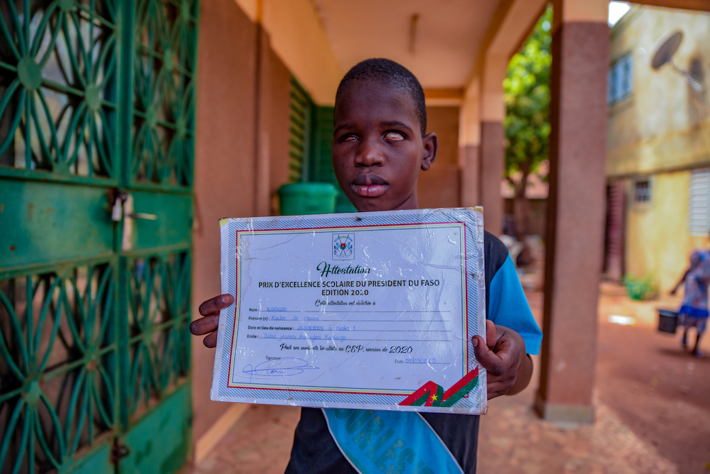 Kader is wearing a blue shirt. He is standing outside his school and is holding up a certificate he received from the president. Kader's school is brown and has green doors.