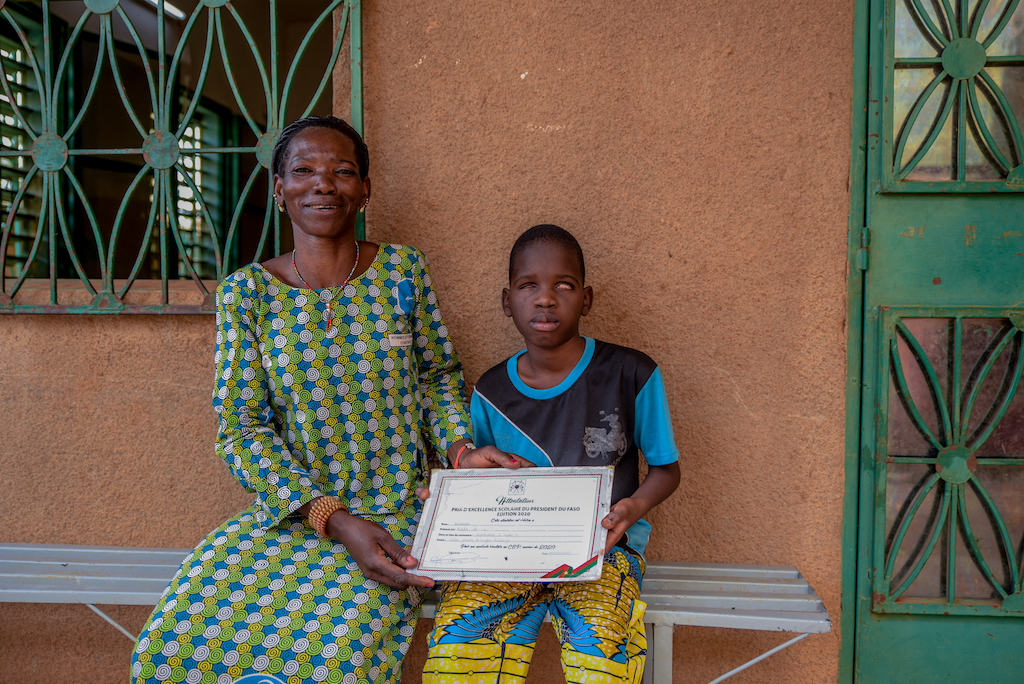 Kader is wearing a blue shirt and yellow patterned pants. He is sitting outside his school next to his mother, Florence, wearing a blue, white, and green dress. They are holding Kader's certificate he received from the president.
