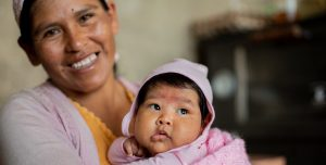A Bolivian mother laughs holds her baby, wrapped in a pink blanket. The mother smiles and laughs.
