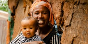 I mother sits outside a mud hut and holds her baby close. They both smile.