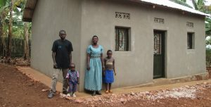 An Ethopian family stands outside of a stucco walled home. There is a mothe, a father and two young children.