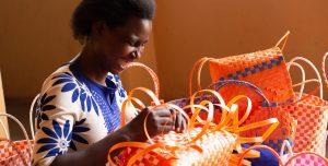 A Ugandan woman laughs as makes a woven bag.