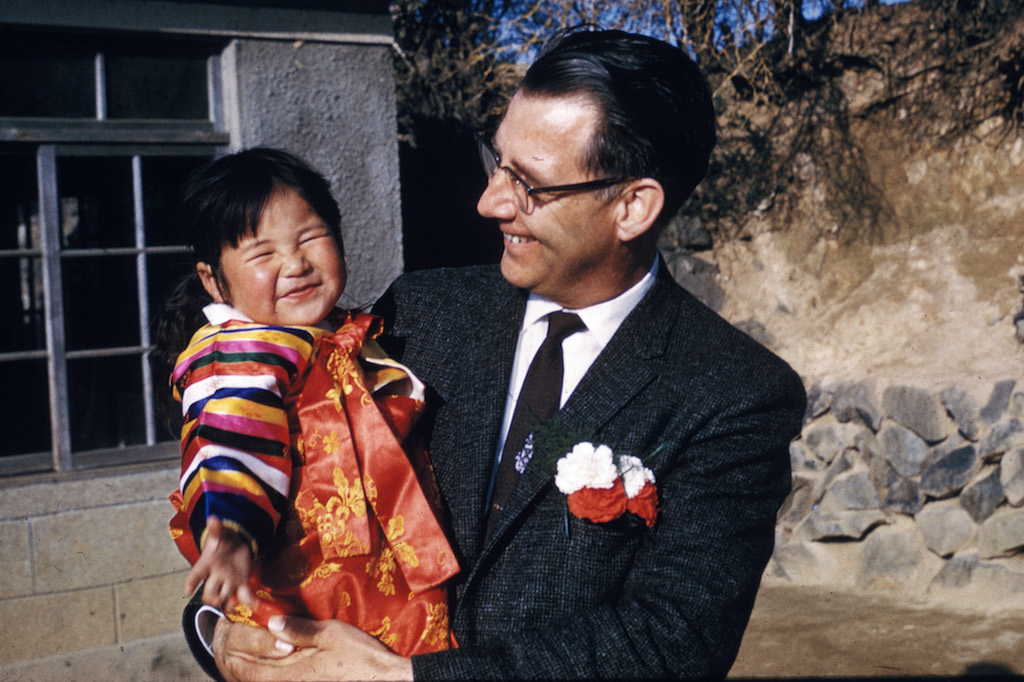 Rev. Swanson is wearing a suit and tie and carrying a Korean toddler in his arms. They are both smiling.