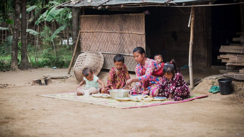 Family sits on a mat outside their home sharing a pot of food.
