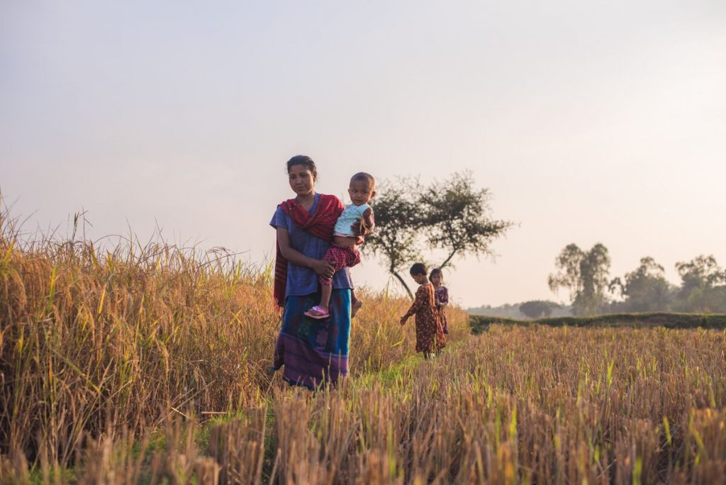A woman carrying a small child walks through the fields with two children close behind.
