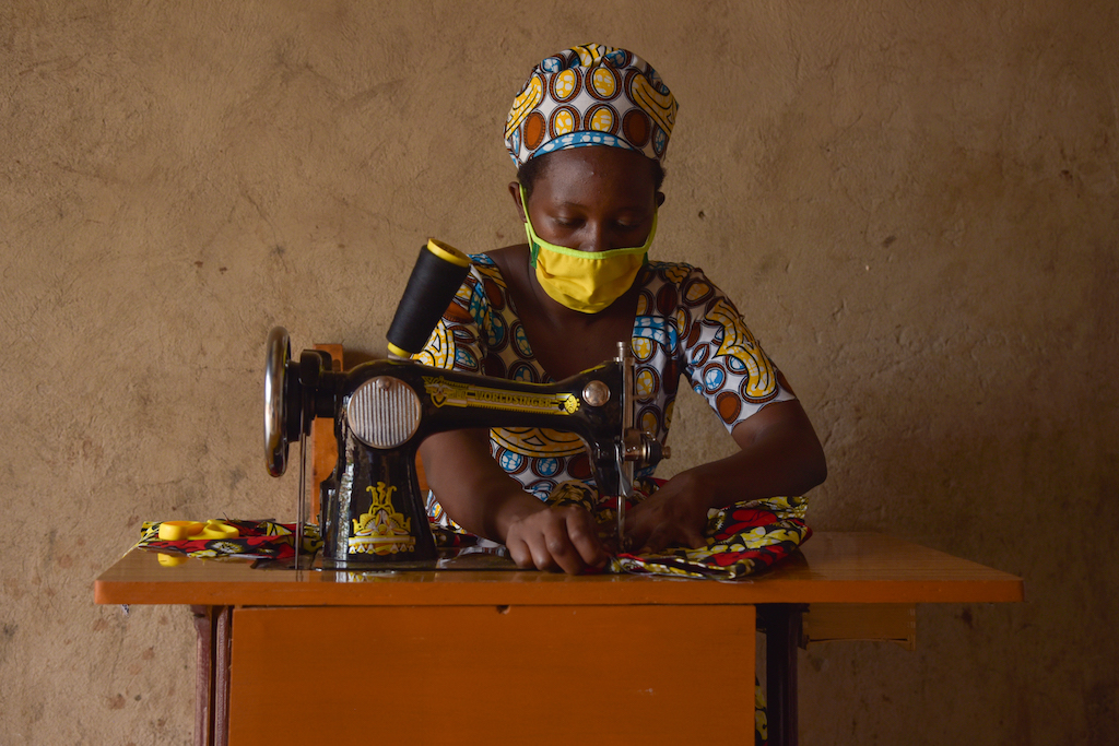 In Rwanda, Alice, the mother of two Compassion sponsored children, is wearing a colorfully patterned dress and a yellow face mask. She is sitting at a sewing machine in her shop and is sewing a dress.