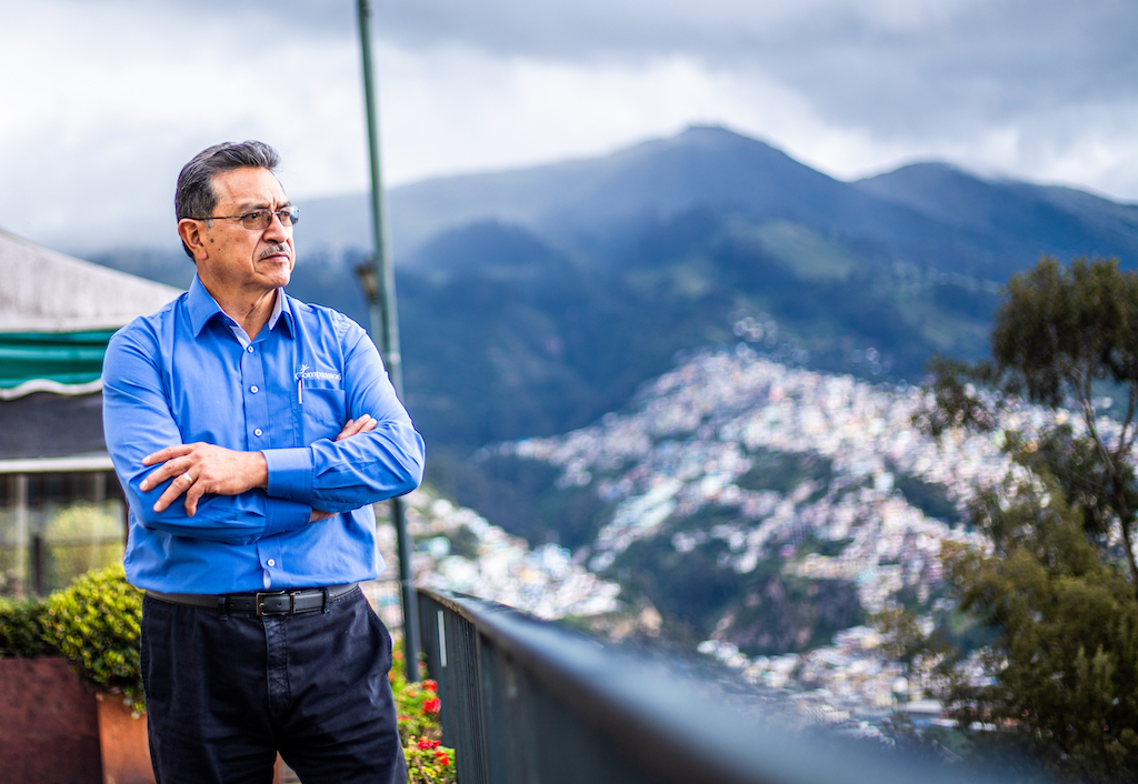 Pastor Sixto Gamboa is wearing a blue shirt. He is standing outside with his arms crossed and is looking out at the mountains in the background.