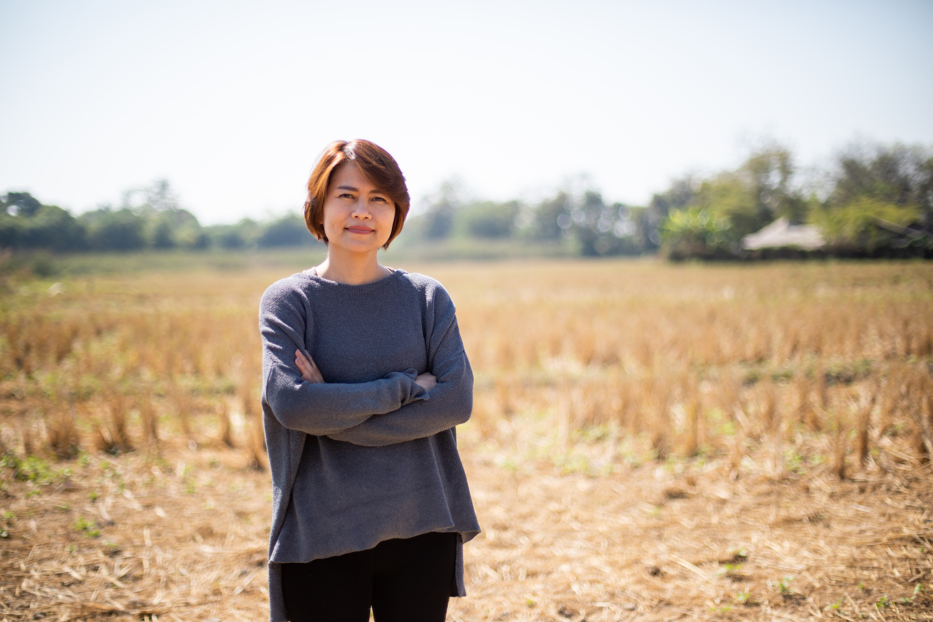 Kriddanchalee, Compassion Thailand's Senior Manager of Program Support, is wearing a gray shirt and is standing on a rice paddy.