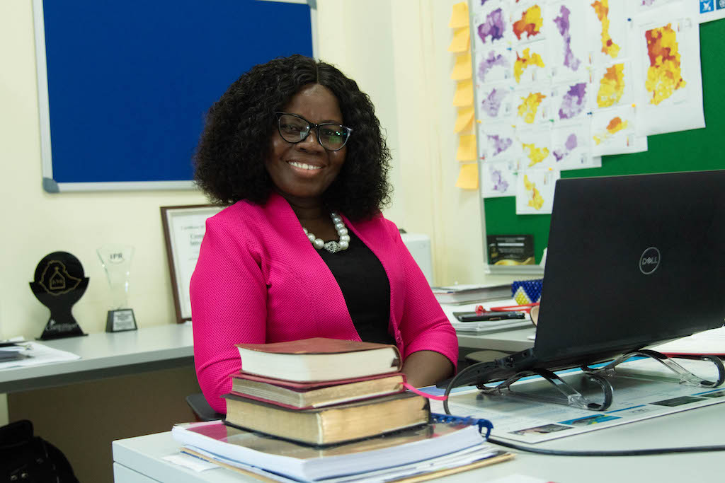 National Director for Ghana, Gifty Appiah, is wearing a black dress and a bright pink jacket. She is sitting at a desk in front of a computer.