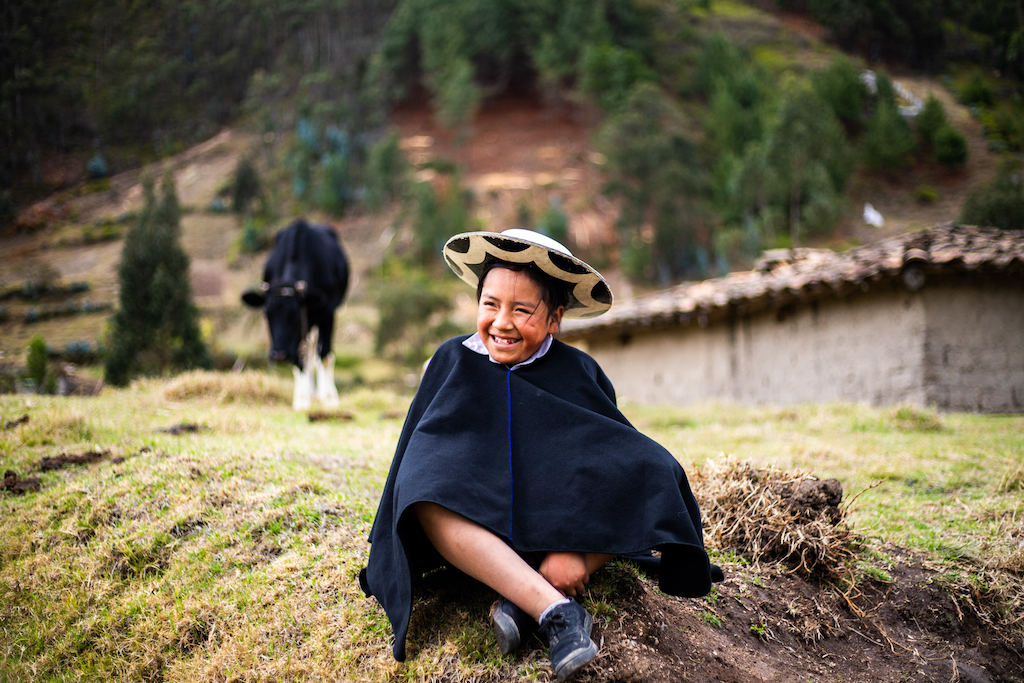In Ecuador, 11-year-old Davis is wearing traditional clothing. He is sitting in a field outside his home. There is a cow behind him.