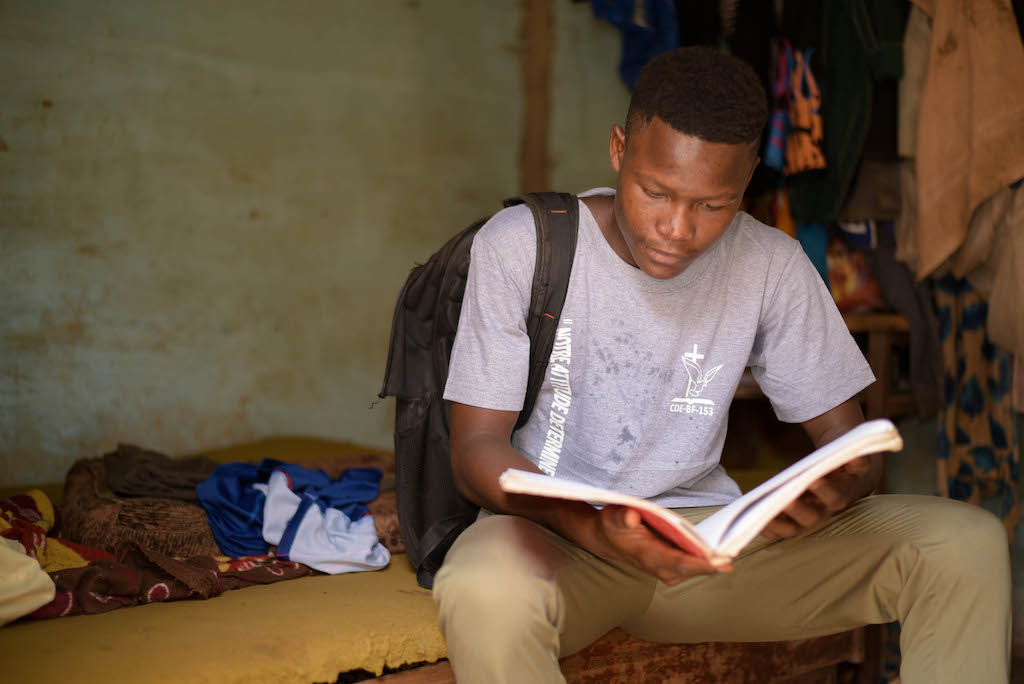 In Burkina Faso, 16-year-old Abdoul is wearing a gray shirt and khaki pants. He is also wearing a black backpack. Abdoul is looking down and reading a book.
