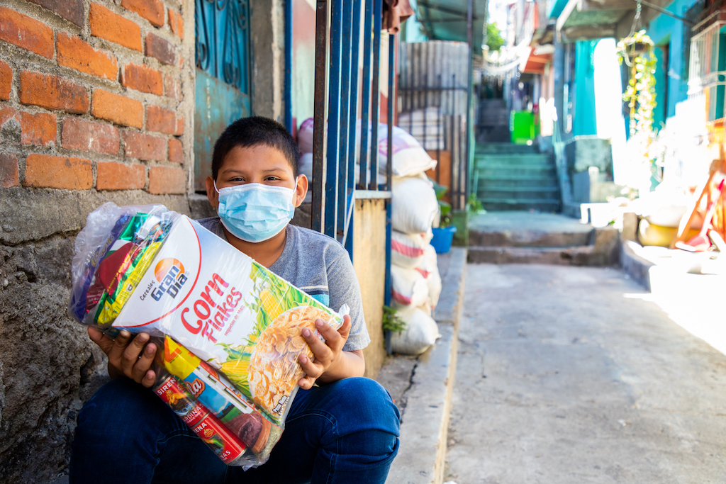 In El Salvador, 11-year-old Jhonny is sitting on the steps in front of his home and is holding a bag of food he was given by the Compassion centre. He is wearing a face mask.