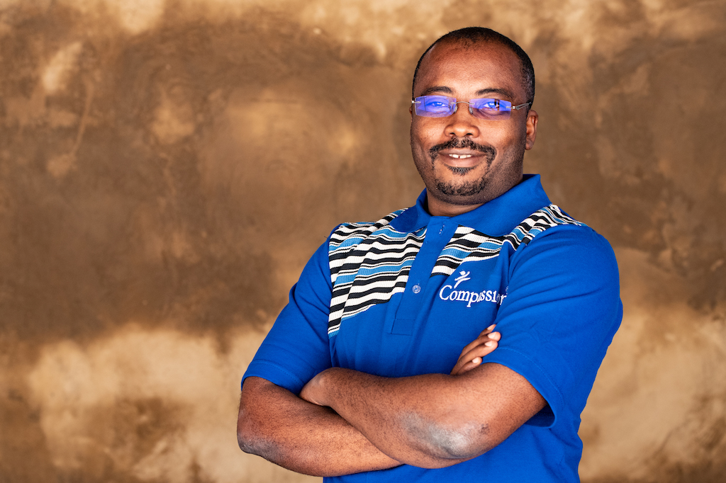 Dr. Issaka Kiemtore is wearing a blue shirt with gray and black stripes and the Compassion logo on the front. He is standing in front of a brown wall with his arms crossed.