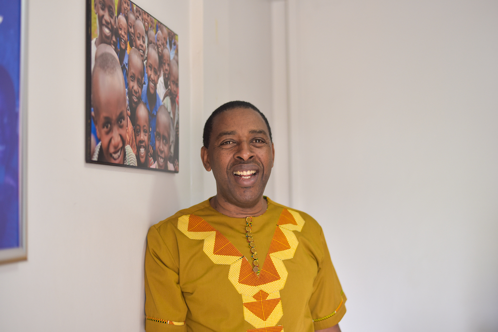 John Nkubana, National Director of Compassion Rwanda, is wearing a gold shirt. He is standing in front of a white wall that has a picture of beneficiary children on it.