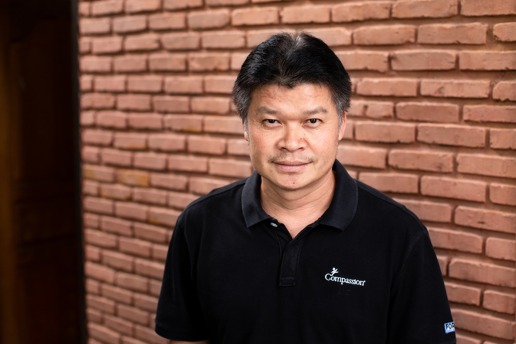 Surachai, Compassion Thailand's Manager of Partnership, is wearing a black shirt and is standing in front of a brick wall.
