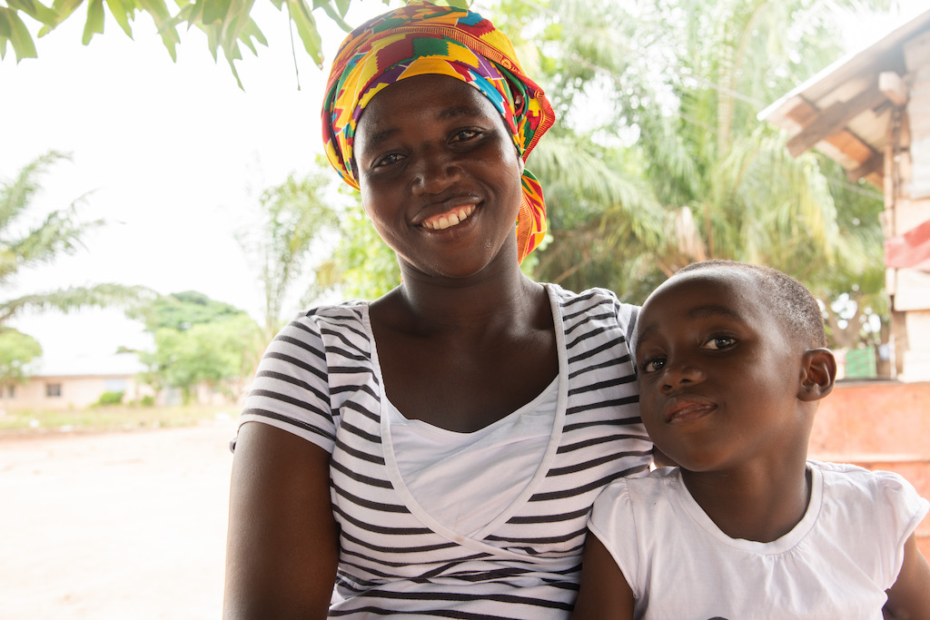 In Ghana, 5-year-old Emmanuella, wearing a white shirt, is sitting outside her home with her mother, Diamatu, wearing a black and white striped shirt and a colorfully patterned head covering.