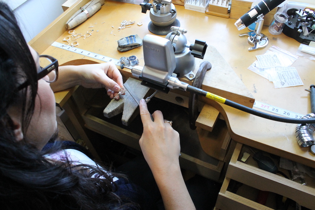 Robin at her workbench using tools to make a key necklace