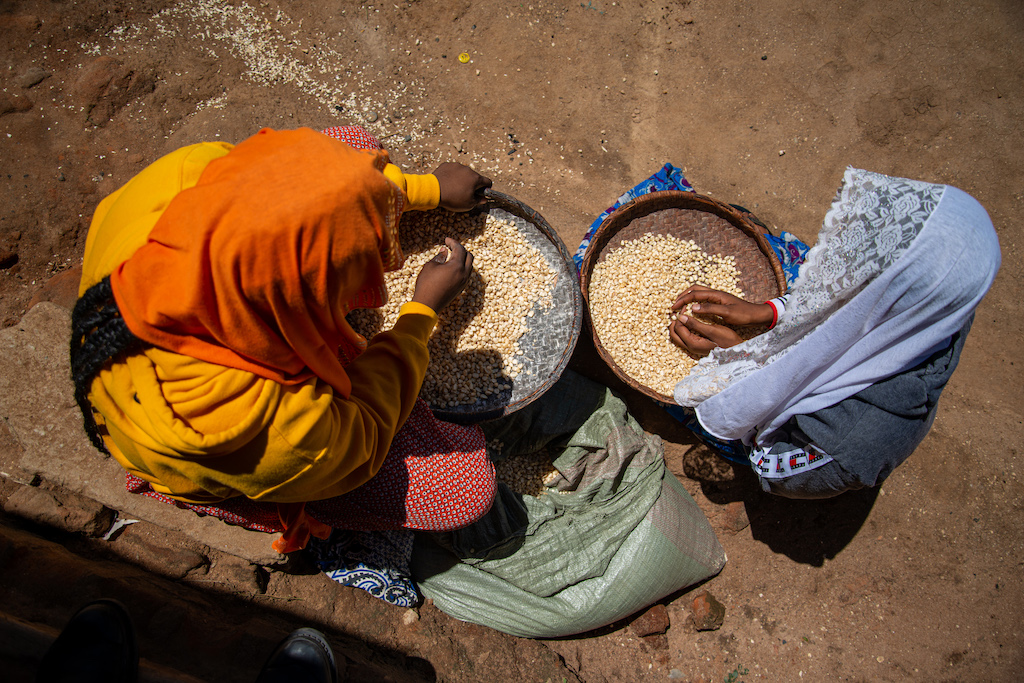 Sarah is on the left wearing a yellow head covering and Maria is on the right wearing a blue head covering.They are outside their home removing chaff from a sack of maize with a winnowing basket.