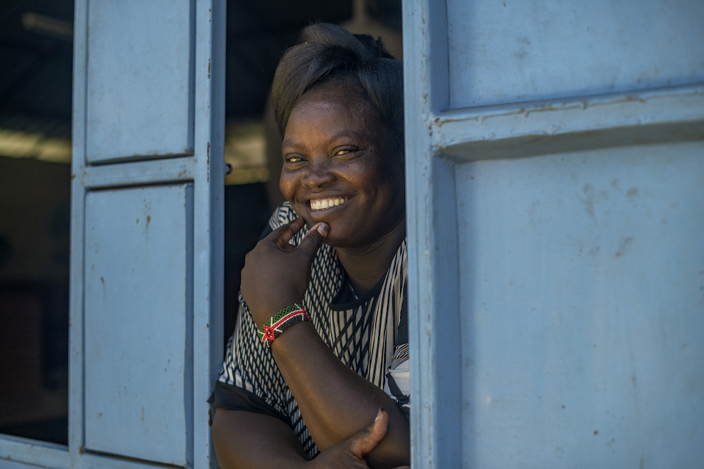 Florence is wearing a black and white dress. She is looking out of a window with blue shutters at the Compassion centre.
