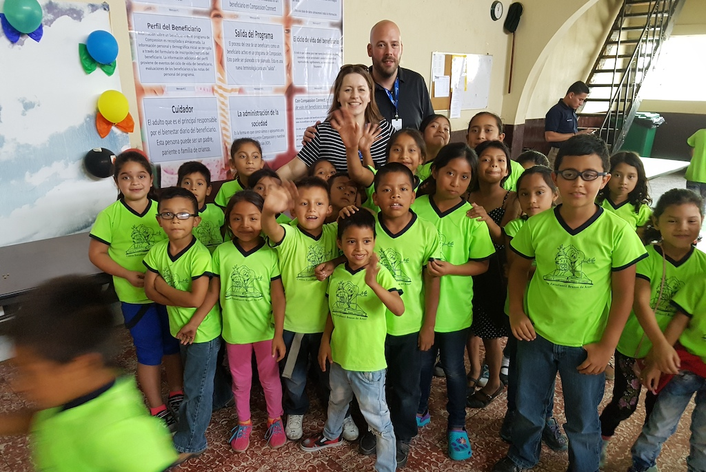 Jeff and Kim with a group of Compassion children all wearing green uniforms.