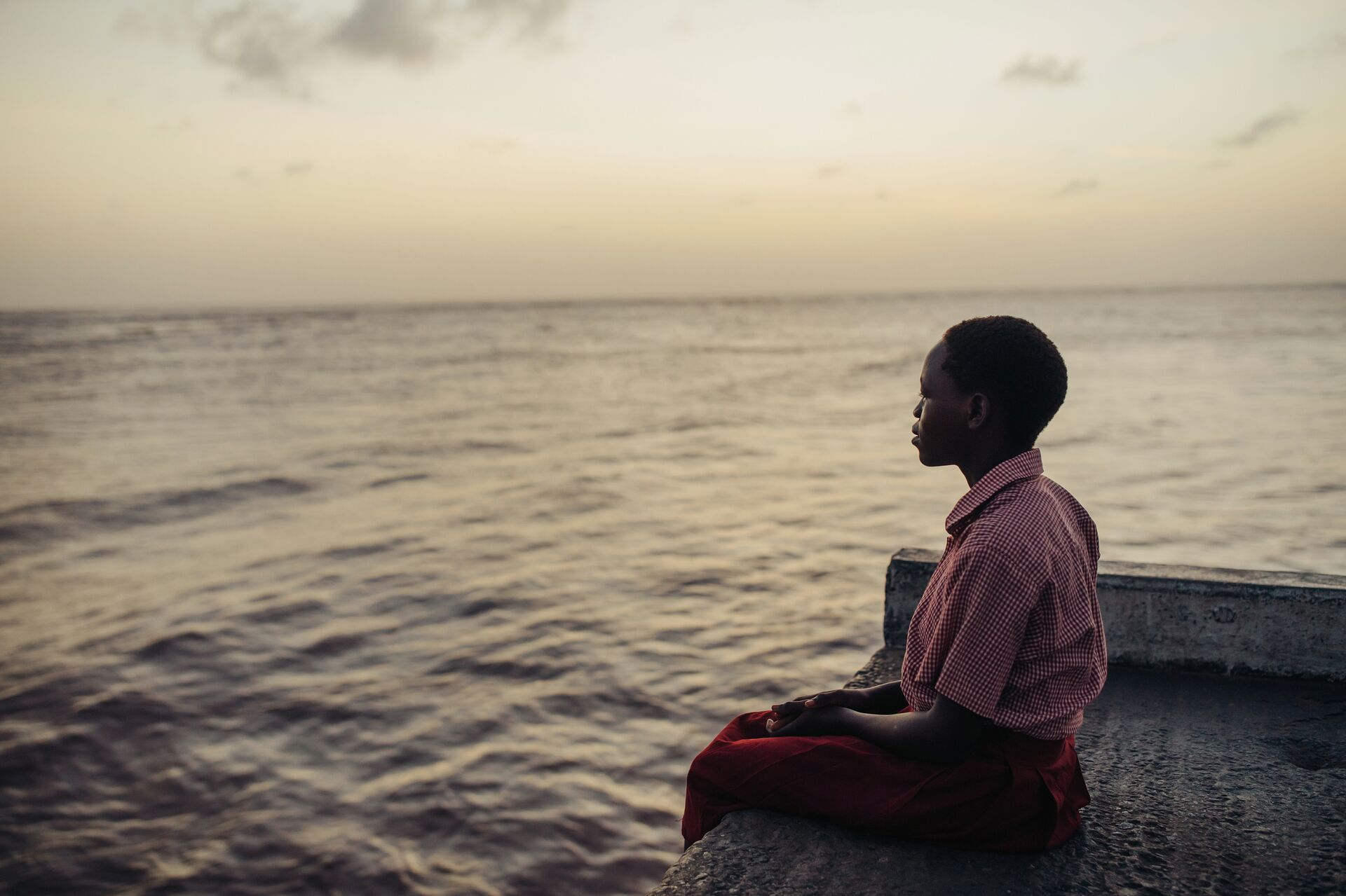 A girl sits on a dock looking out onto the water at dusk.