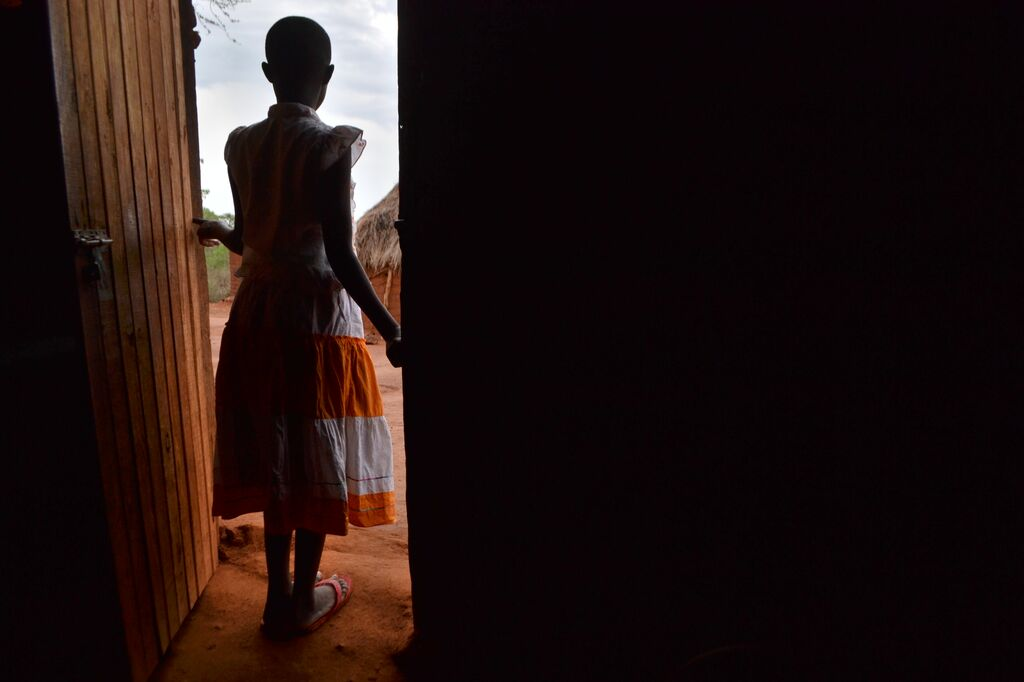 Girl stands facing away at the silhouette of her lit doorway at home crop