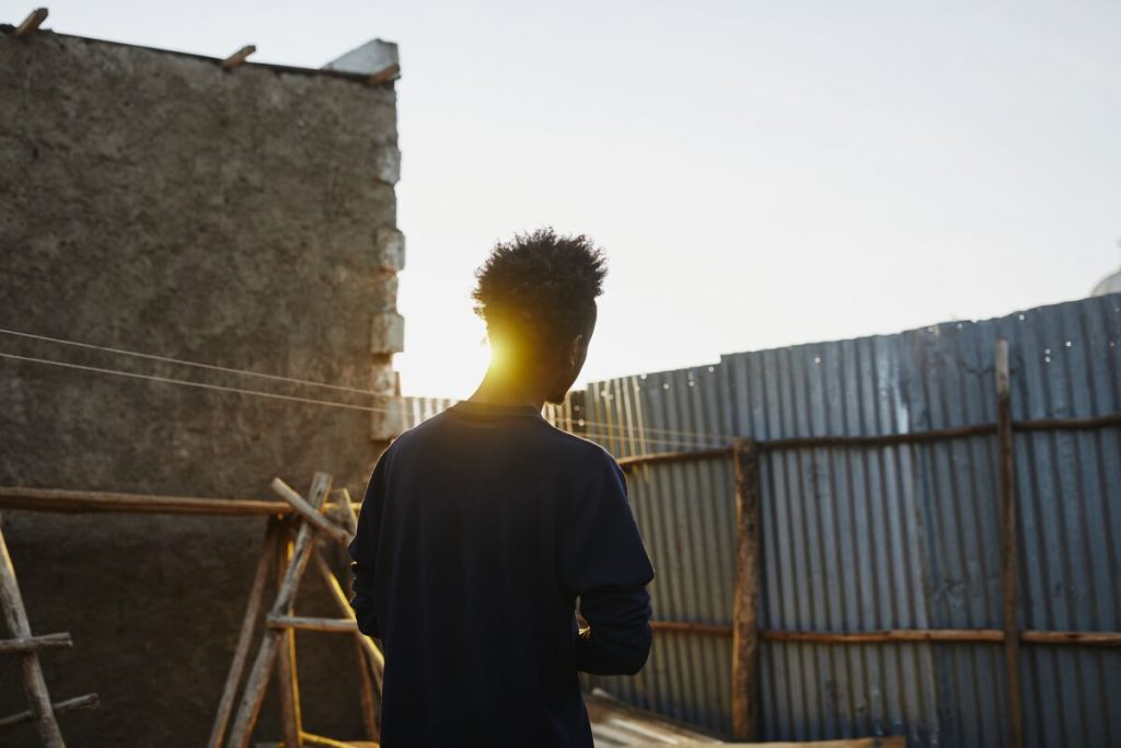 Young man walks passed a brick wall with the sun peaking through.