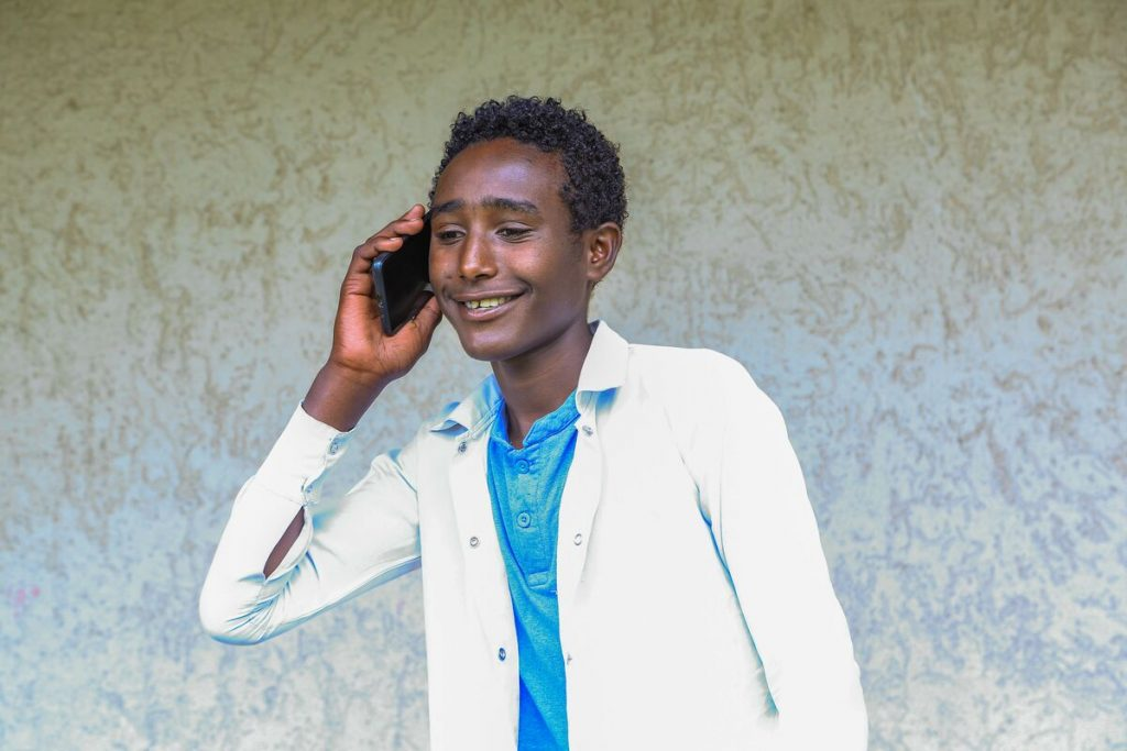 Young man talks on the phone while smiling.