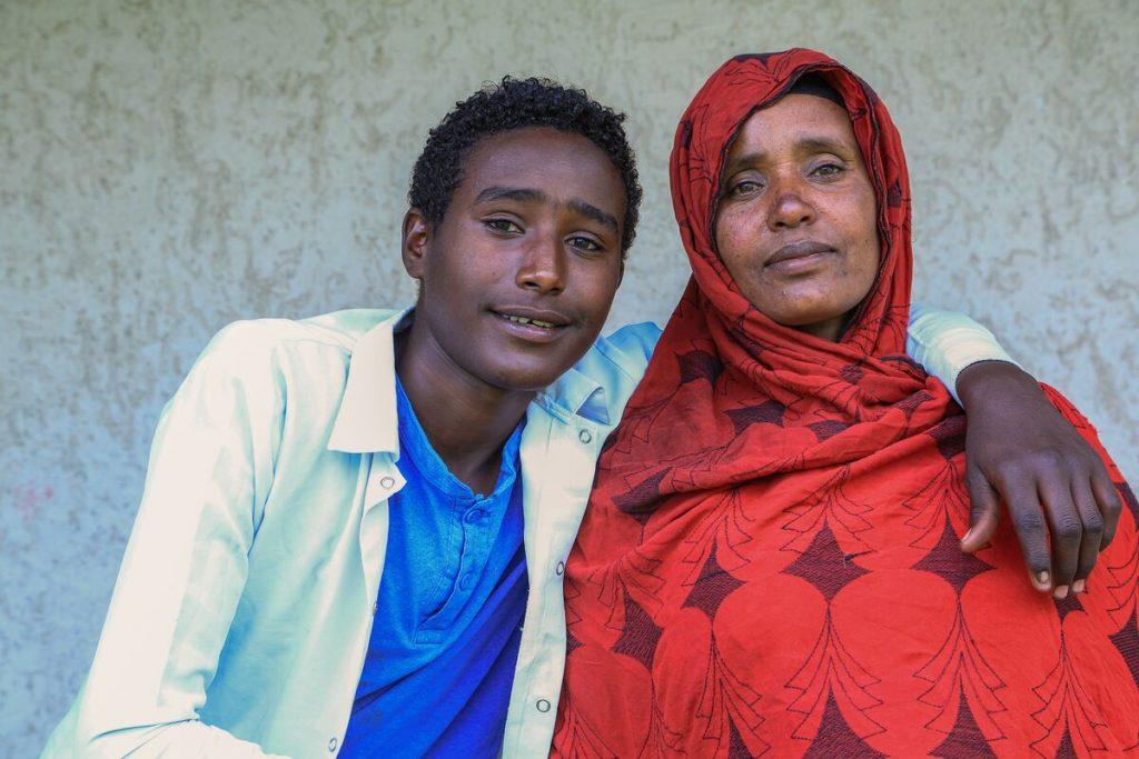 Sadam and his mom pose together for a photo.