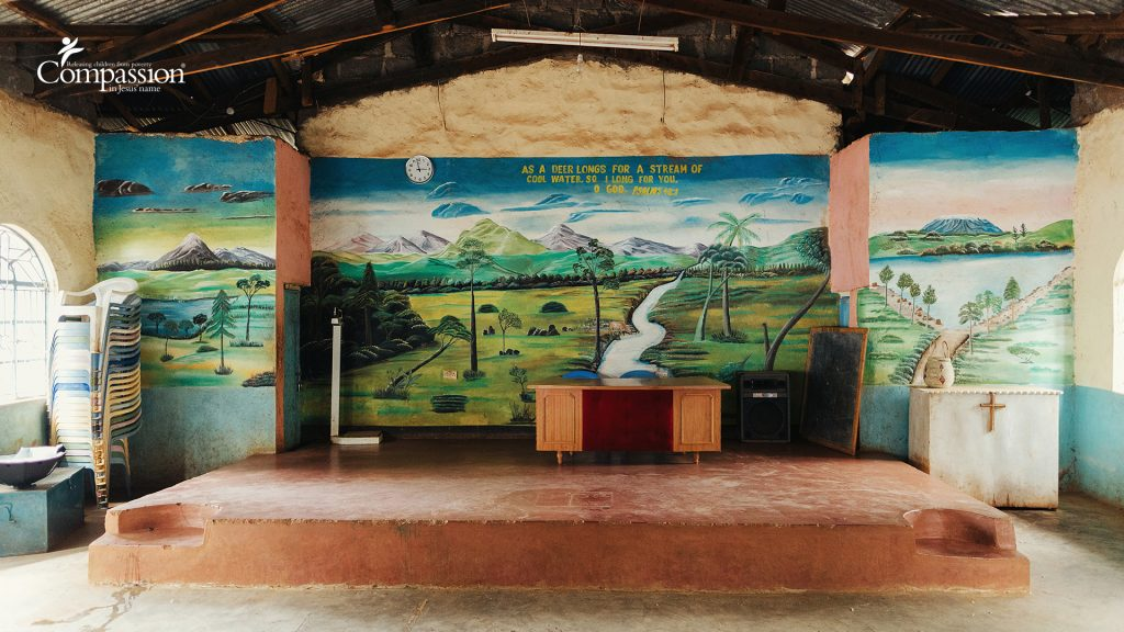 The front of a church sanctuary with a mural.