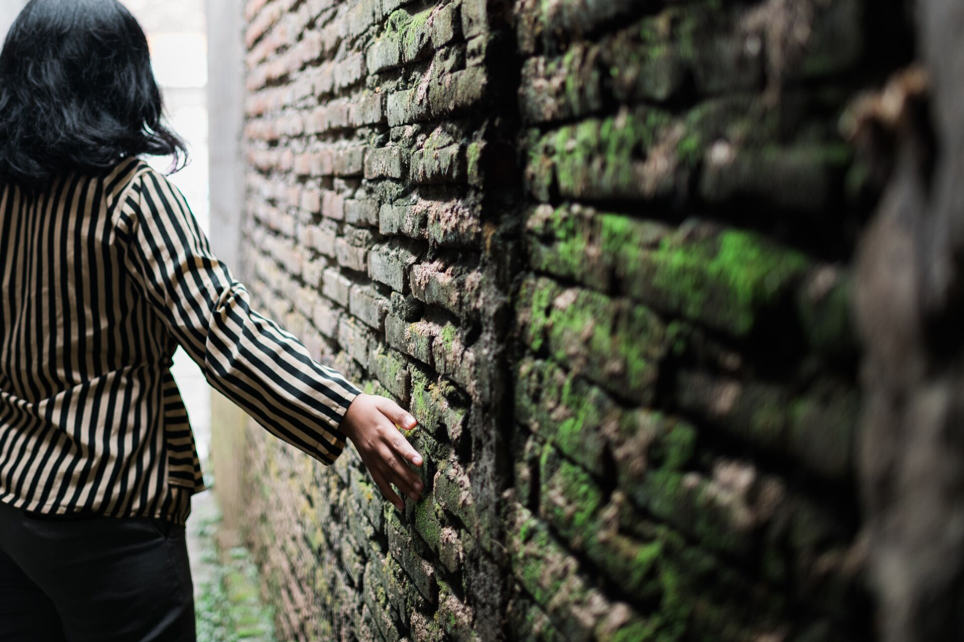 Girl walks down an alleyway with her hand running against the moss covered wall