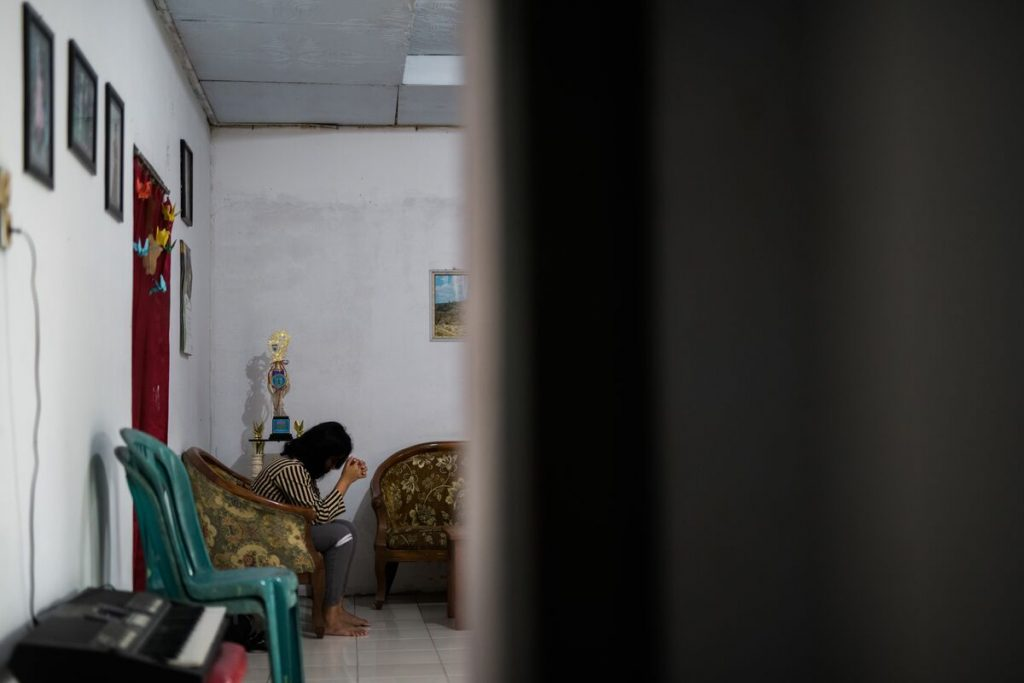 A far away picture of a girl sitting on a chair leaned over and praying.