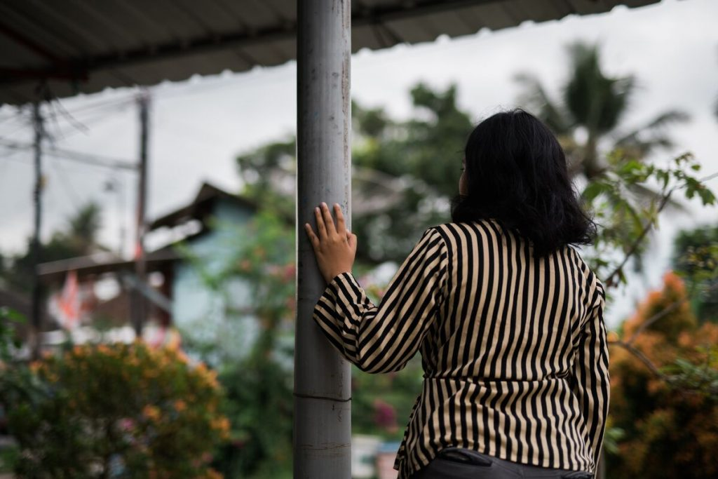 Girl in a stripped shirt walks through the street, her hand on a pole.