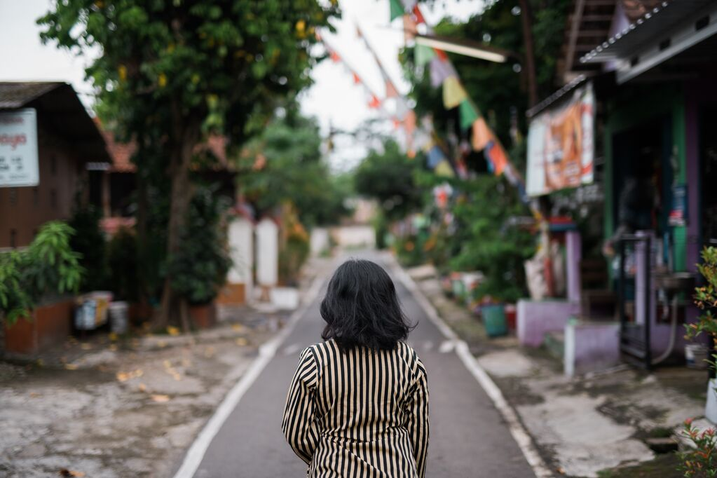 Girl in stripped shirt walks down street with houses on either side. There are flags across the road