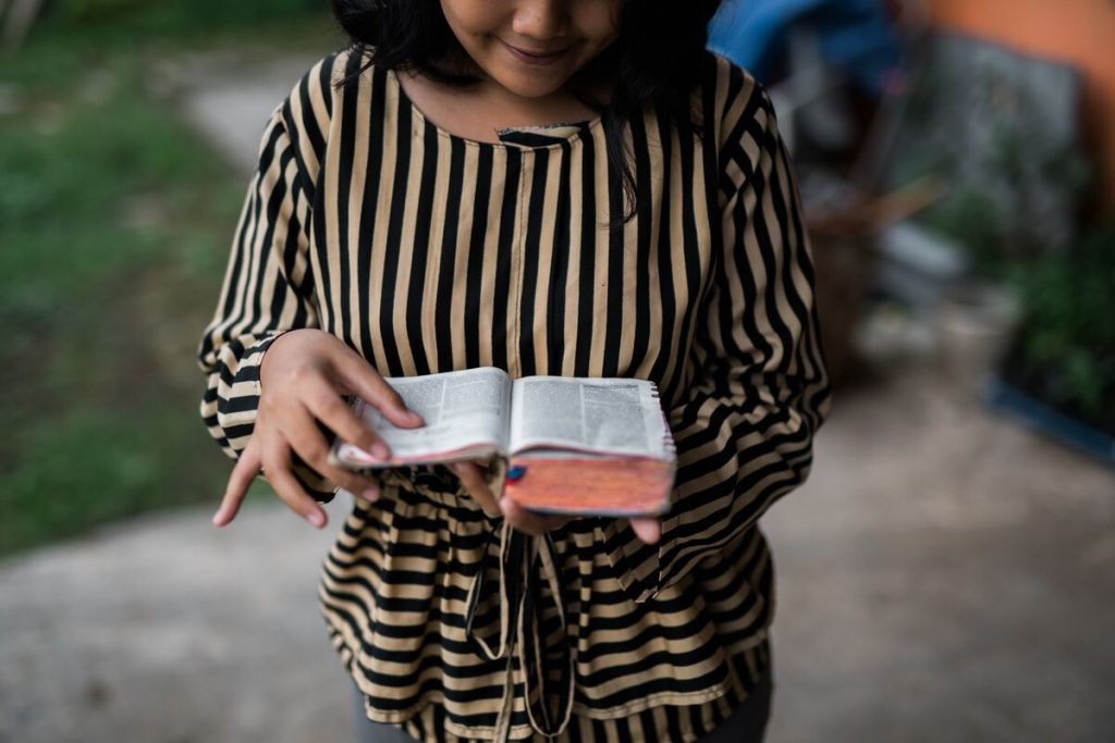 Girl in stripped shirt is pictures with her bible open reading a verse.