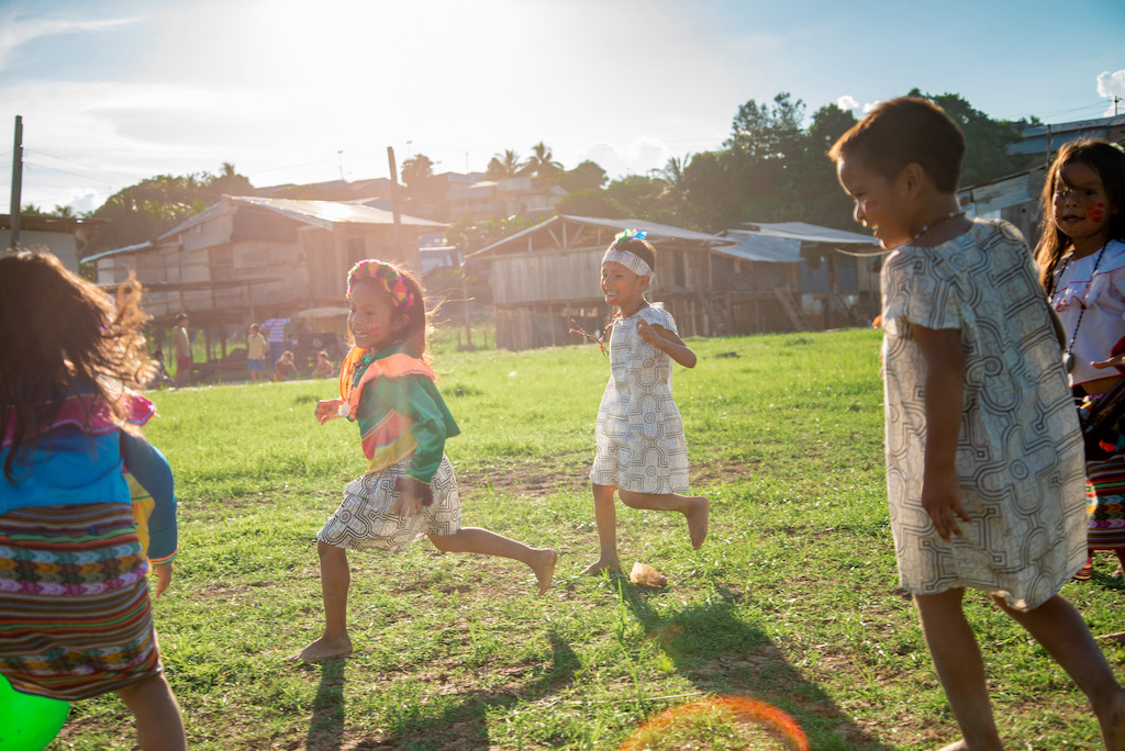 Children of the Shawi tribe run in a field, wearing their colourful traditional clothing.