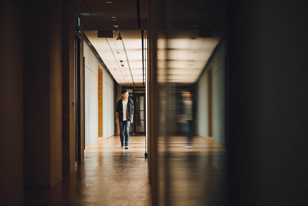 A young man walks down a hallway.