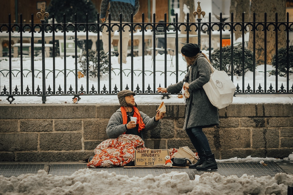 A woman hands something to a man sitting on the street.