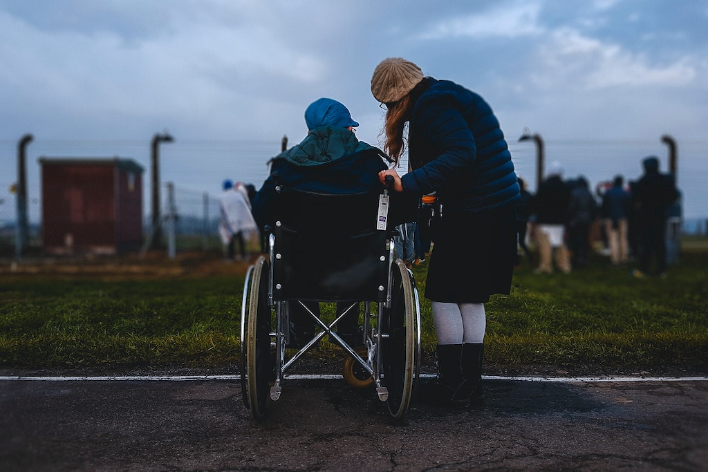 A woman stands beside another woman who is using a wheelchair.