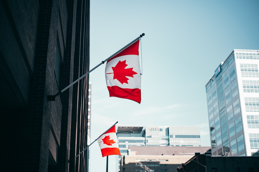 A building with Canadian flags hanging on it.