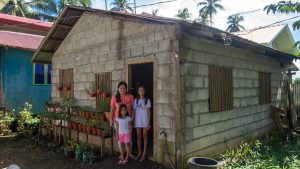 A mother and her two children stand outside a cinder block home.