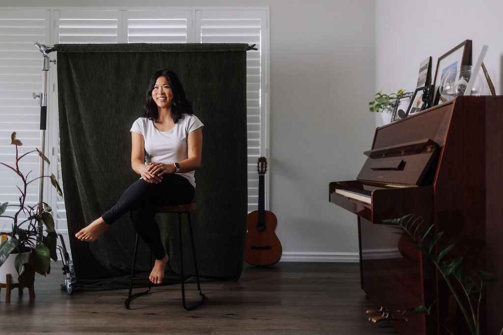 Portrait of Lara in her home. She is wearing a white shirt and black pants. Lara is sitting in front of a green curtain. There is a guitar behind her.