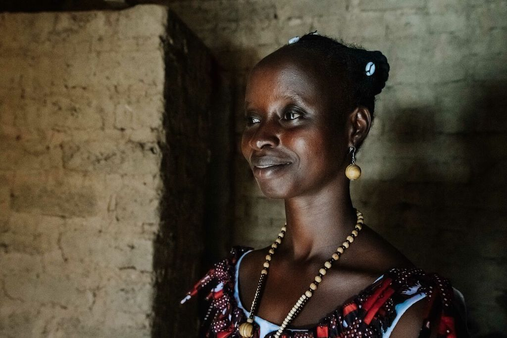 Beatrice is standing inside her mud brick home and is looking outside.
